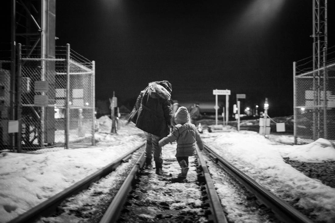 Two asylum seekers, a woman and young girl, cross the Canadian border, in Noyes, Minn.