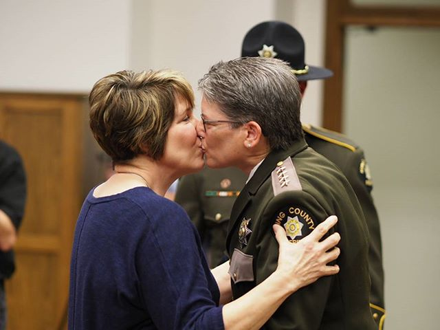 New King County Sheriff Mitzi Johanknecht shares a kiss with her wife Maureen Warren following her swearing-in
