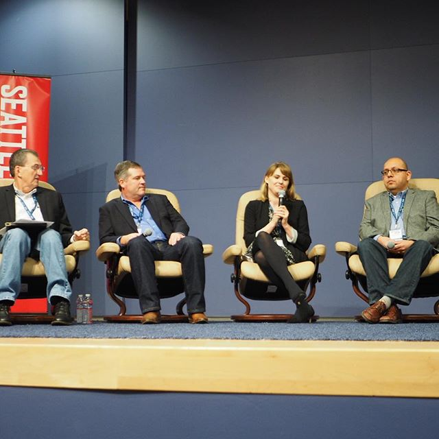 """Kelli Scott of the Wenatchee World speaks during the """"Bridging the Cascade Divide"""" panel at #crosscutfest while other panelists Stuart Elway, Rep. J.T. Wilcox, and Judge David Estudillo listen."""