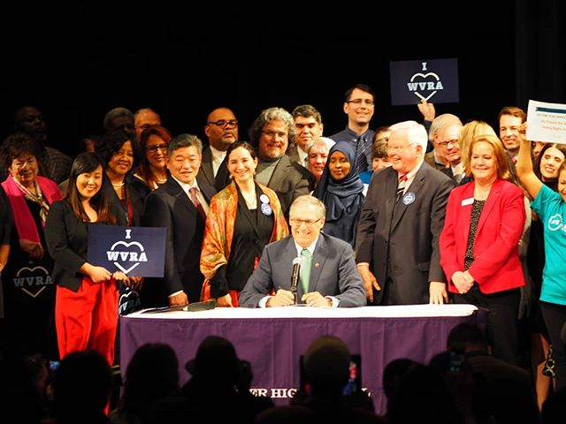 Governor Inslee and pro-democracy activists celebrate the signing of the Access to Democracy package