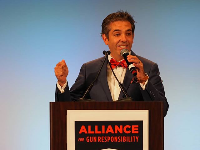 Auctioneer and comedian Fred Northup, Jr. invites Alliance for Gun Responsibility luncheon attendees to raise their bid cards