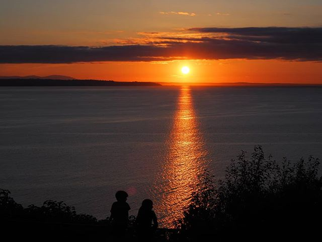 Two children watch the sun set on the longest day of the year ? Happy summer from NPI!