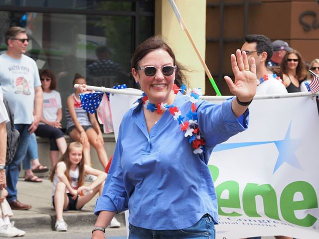 U. S. Representative Suzan DelBene waves to onlookers while marching in Kirkland's Fourth of July Hometown Hero Parade