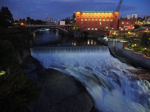 Avista's Spokane River hydroelectric generating facility on Monroe Street, seen at night, with the iconic Washington Water Power Building in the background