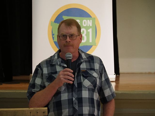 Retired oil refinery worker Steve Garey gives an in-person pitch for Initiative 1631