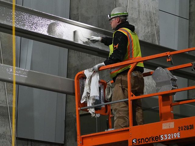 Inside the forthcoming Roosevelt Link light rail station: A worker applies paint