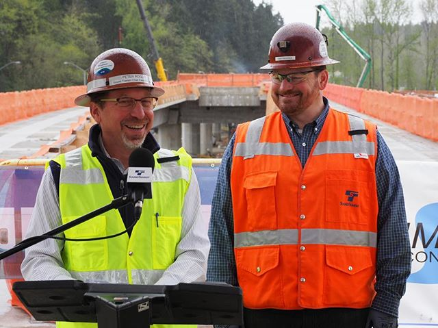 Sound Transit's Peter Rogoff and Chad Frederick share a laugh at a news conference announcing that East Link has reached the 50% construction milestone