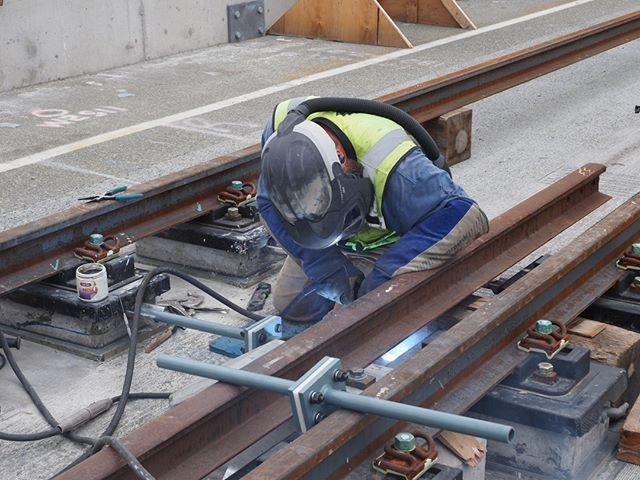 A welder installs tie rods on the Homer M. Hadley Memorial Bridge