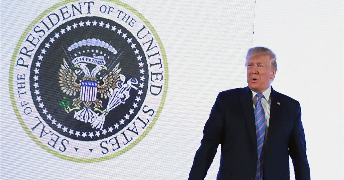 Donald Trump in front of a fake seal