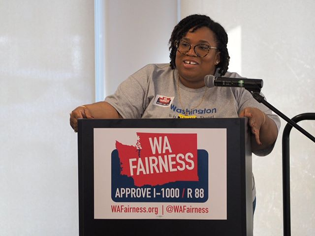 Washington Fairness Coalition manager Cherika Carter speaks at a Get Out The Vote rally in Seattle, urging an Approved vote on I-1000/R-88