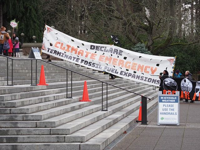 A Declare Climate Emergency banner is hoisted up the steps of Washington State's Legislative Building on the first day of the 2020 session