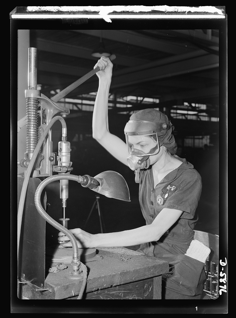 A million dollar baby, not in terms of money but in her value to Uncle Sam, twenty-one-year-old Eunice Hancock, erstwhile five-and-ten-cent store employee, operates a compressed-air grinder in a Midwest aircraft motor plant. With no previous experience, Eunice quickly mastered the techniques of her war job and today is turning out motor parts with speed and skill. Note protective mask and visor, two vital safety accessories