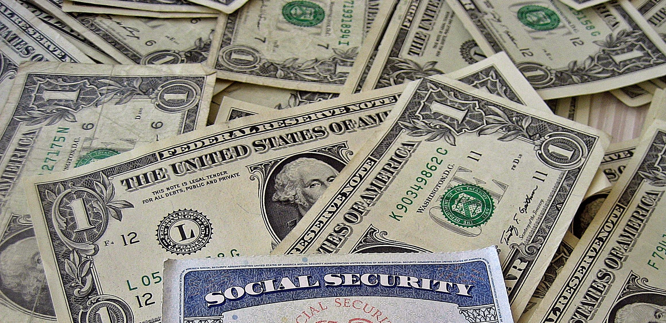 Social Security card on top of a bed of money