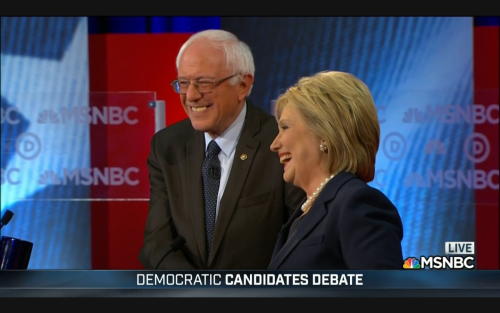 Bernie Sanders and Hillary Clinton shake hands and smile
