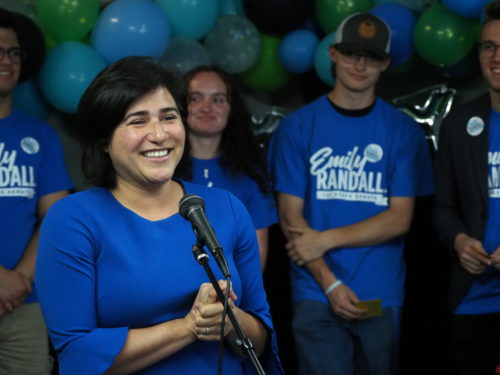 Emily Randall speaks at her campaign kickoff, flanked by her campaign team