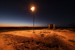 A gas flare burns bright on a production site northeast of Andrews, Texas.