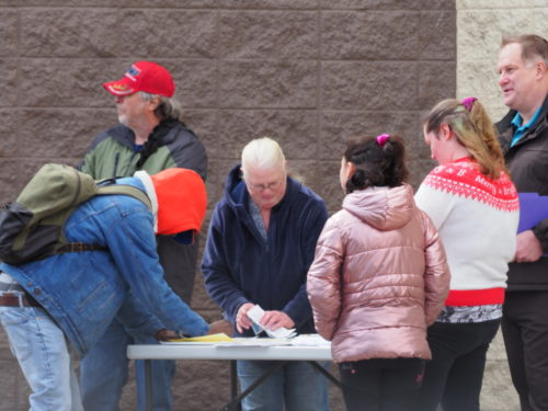 People congregating around a petition table