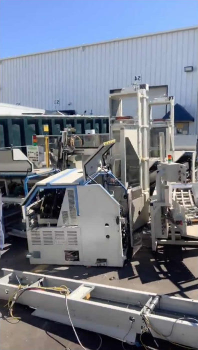 Dismantled mail sorting machines in a parking lot