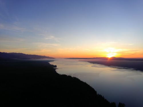 The sun rises over Hood Canal and the Olympics